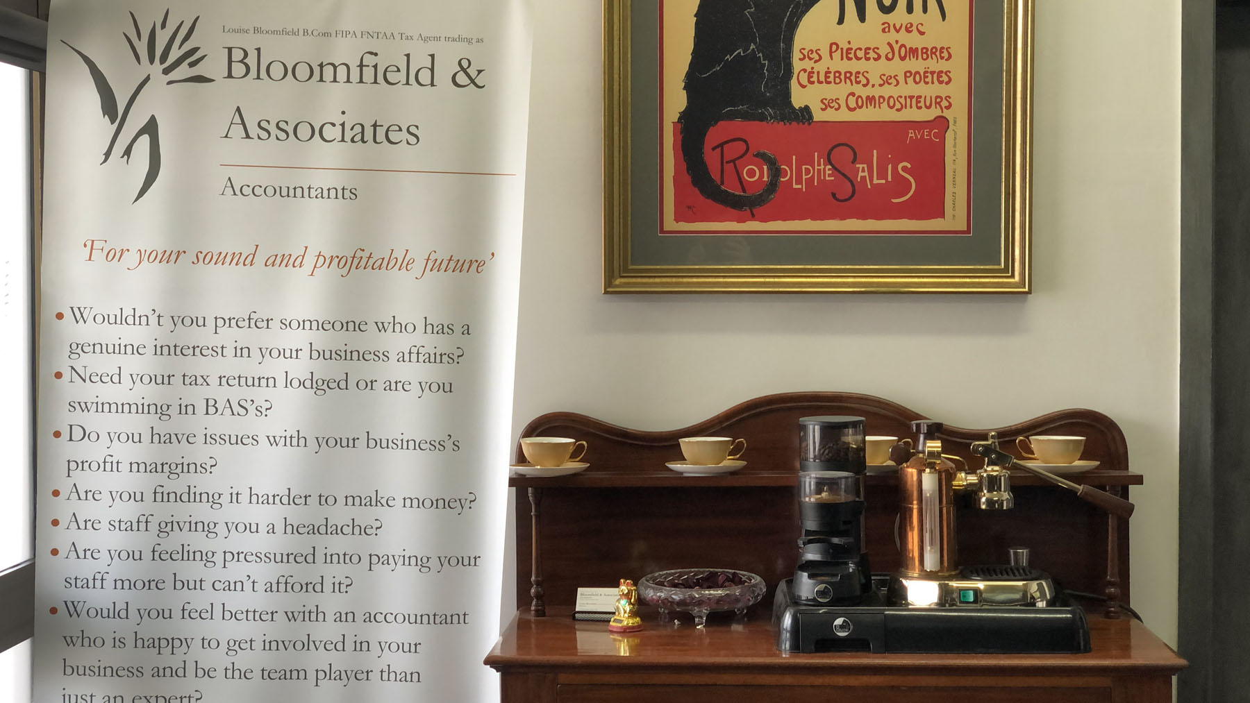 Bloomfield & Associates coffee machine on wooden cabinet with pull-up banner to the left